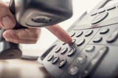 Close up da mão masculina que guarda o receptor de telefone ao discar a imagem de stock