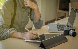 Close-up da mão masculina, usando a tabuleta, o computador e a câmera digitais Imagem de Stock