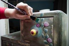 Close up da mão da mulher com o armário de madeira da pintura da escova diy Fotografia de Stock Royalty Free