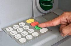 Close-up da mão que dá entrada ao código de PIN/pass no keyp da máquina de ATM/bank Foto de Stock