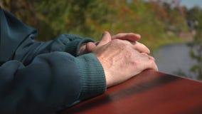 Close up da mão superior do ancião contra o fundo bonito do rio da floresta da natureza filme