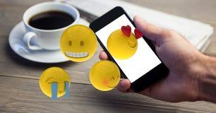 Close-up da mão usando o telefone esperto quando emojis que voam sobre a tabela ilustração stock