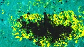 Close-up da mancha amarela da tinta e de gotas de queda pretas da tinta em um fundo do gel de turquesa Arte e texturas video estoque