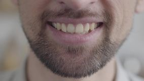 Close-up da maxila mais baixa de um homem farpado triste adulto que tenta sorrir com um sorriso forçado Humor negativo, problemas video estoque