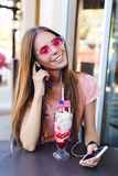 Close-up da menina bonito que senta-se em um café que come o gelado com a cereja na parte superior Veste monóculos superiores e c imagens de stock royalty free