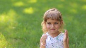 Close-up da menina com os olhos multi-coloridos que sentam-se no parque do verão na grama video estoque