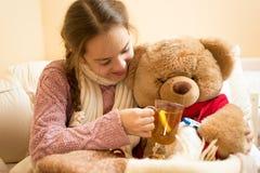 Close up da menina doente pequena que dá o chá quente ao urso de peluche Fotografia de Stock Royalty Free