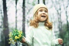 Close up da menina que cheira uma flor amarela em um fundo verde feliz Foto de Stock Royalty Free