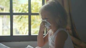 Close-up da menina que funde e que limpa seu nariz com um guardanapo sanitário filme