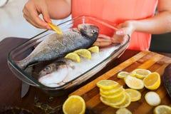 Close-up da menina que põe partes de limão nos peixes Foto de Stock Royalty Free