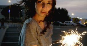 Close up da menina temperamental com queimadura de luzes de bengal em suas mãos video estoque