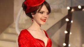 Close up da moça bonita da forma no chapéu retro e no vestido vermelho, modelo moreno com a composição vermelha dos bordos, elega vídeos de arquivo