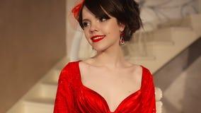 Close up da moça bonita da forma no chapéu retro e no vestido vermelho, modelo moreno com a composição vermelha dos bordos, elega video estoque