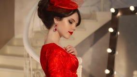 Close up da moça bonita da forma no chapéu retro e no vestido vermelho, modelo moreno com a composição vermelha dos bordos, elega filme