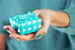 Close-up da mão fêmea que guarda um presente Foto de Stock