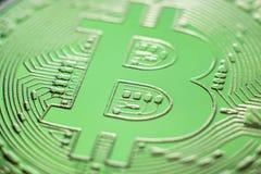 Close up da moeda da moeda de Bitcoin na luz verde foto de stock royalty free