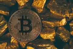 Close up da moeda digital do bitcoin e da pepita de ouro ou minério do ouro no fundo preto, na pedra preciosa ou na protuberância imagem de stock