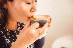 Close up da mulher asiática que senta-se em um café e em um café da bebida Fotografia de Stock