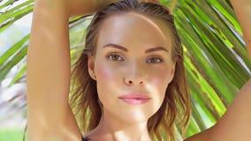 Close up da mulher bonita do encanto que veste o roupa de banho preto que levanta em um dia de verão bonito entre palmeiras Foto de Stock