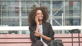 Close-up da mulher de negócio afro-americano de sorriso nova atrativa que senta-se no banco no aeroporto e que fala sobre filme