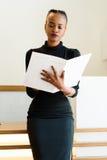 Close-up da mulher de negócio americana africana ou preta bem sucedida que guarda e que olha o arquivo branco grande Imagem de Stock