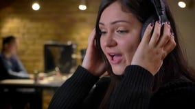 Close up da mulher de negócios caucasiano alegre nos fones de ouvido que escuta o sorriso da música e do canto e a apreciação filme