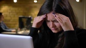 Close up da mulher de negócios caucasiano moreno adulta que trabalha no portátil e que obtém uma dor de cabeça cansada video estoque
