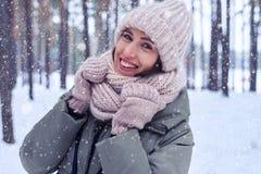 Close-up da mulher de sorriso que olha a câmera em um colo nevando Fotografia de Stock Royalty Free