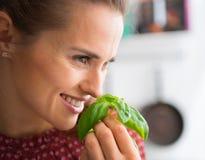 Close up da mulher de sorriso que sustenta e que cheira a manjericão fresca imagens de stock
