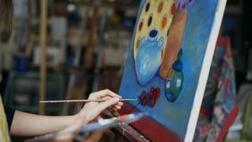 Close-up da mulher do artista com a escova que pinta ainda a imagem da vida na lona na arte-classe Imagens de Stock Royalty Free