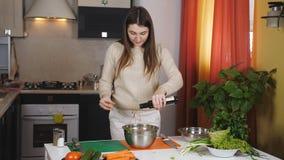 Close-up da mulher do vegetariano que prepara a salada crua derramando o azeite em vegetais e adicionando a pimenta em de madeira filme