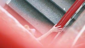 Close-up da mulher loura bonita no t-shirt branco, nas cal?as de brim e na liga??o em ponte preta escalando as escadas na entrada vídeos de arquivo