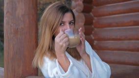 Close up da mulher no roupão que bebe o café quente na varanda da casa de madeira filme