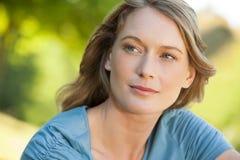 Close-up da mulher pensativa que olha afastado no parque imagem de stock