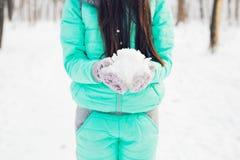 Close-up da mulher que guarda a neve branca macia natural em suas mãos para fazer uma bola de neve, sorrindo durante um dia de in Fotos de Stock Royalty Free
