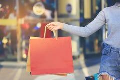 Close up da mulher que guarda sacos de compras com posição no depa imagem de stock