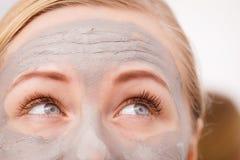 Close up da mulher que tem a máscara cinzenta da lama na cara imagens de stock