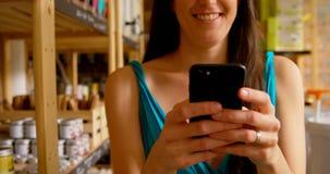 Close-up da mulher que usa o telefone celular no supermercado 4k video estoque