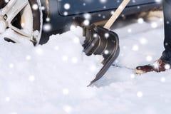 Close up da neve de escavação do homem com a pá perto do carro Imagens de Stock Royalty Free