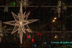 Close-up da parte de grande estrela decorativa do Natal no fundo de janelas brilhantes da loja Natal generoso e rico fotografia de stock royalty free