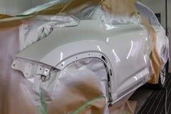 Close-up da parte dianteira do corpo da asa desmontada do carro após o reparo e do branco de pintura na oficina, o resto de fotos de stock royalty free