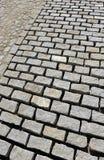 Close up da pavimentação de uma rua na cidade espanhola de Sevilha com as pedras de pavimentação do granito e o almofariz do cime imagens de stock