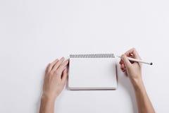 Close-up da pena fêmea da escrita da mão em um caderno vazio Imagem de Stock Royalty Free