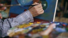 Close-up da pintura da mão do ` s do artista na lona na oficina da arte filme