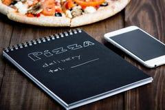 Close-up da pizza, de um telefone celular e de um caderno com o texto: Entrega da pizza tabela de madeira do fundo Preto do cader imagens de stock