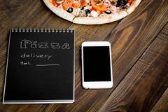 Close-up da pizza, de um telefone celular e de um caderno com o texto: Entrega da pizza tabela de madeira do fundo Preto do cader imagens de stock royalty free