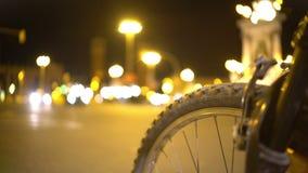Close-up da roda de bicicleta, timelapse defocused do tráfego da noite, transporte urbano vídeos de arquivo