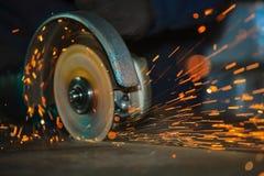 Close-up da rotação do moedor de ângulo do disco durante a operação Faíscas brilhantes do corte do metal imagem de stock royalty free