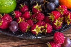 Close-up da salada de fruto com framboesas, uva, cal em uma placa da argila em uma tabela de madeira rústica, vista de cima de, m fotos de stock royalty free