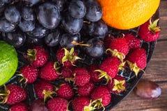 Close-up da salada de fruto com framboesas, uva, cal em uma placa da argila em uma tabela de madeira rústica, vista de cima de, m foto de stock royalty free